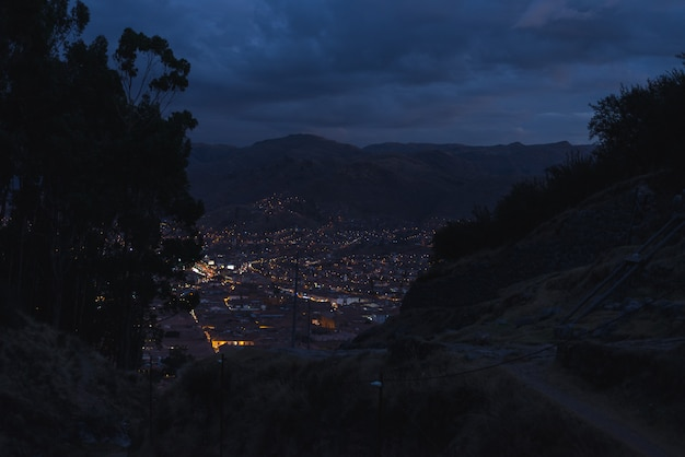 Panoramic view of cusco town with glowing city lights at dusk. cusco is among the most touristy travel destination in peru and south america.