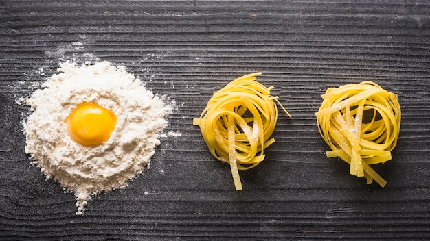 Panoramic view of egg yolk with white flour and raw tagliatelle on wooden backdrop