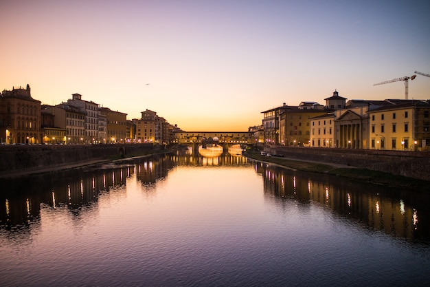 Panoramic view of famous ponte vecchio with river arno at sunset in florence, italy