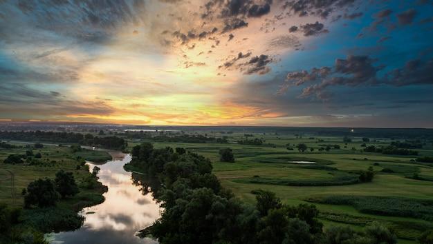 劇的なカラフルな空、素晴らしい夕日の幻想的な風景の丘からのパノラマビュー