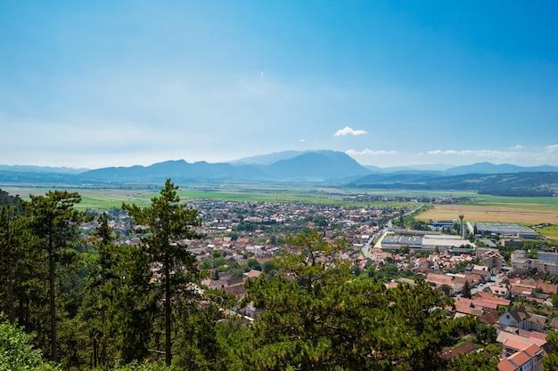 Панорамный вид с вершины цитадели рышнов, четатеа рышнов, на город и румынские карпаты вдалеке в летний солнечный день. страна брашов, трансильвания, румыния
