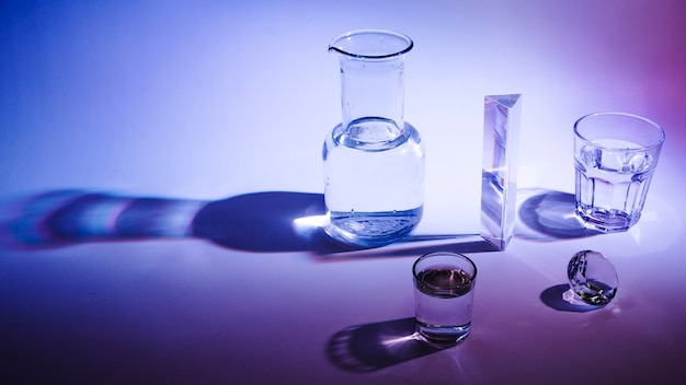 Panoramic view of glass; beaker; prism and diamond with dark shadow on bright background