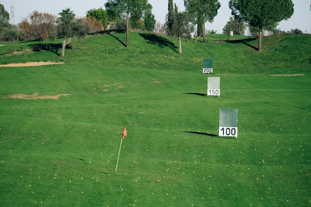 Panoramic view of a golf practice course with signs of meters reached.