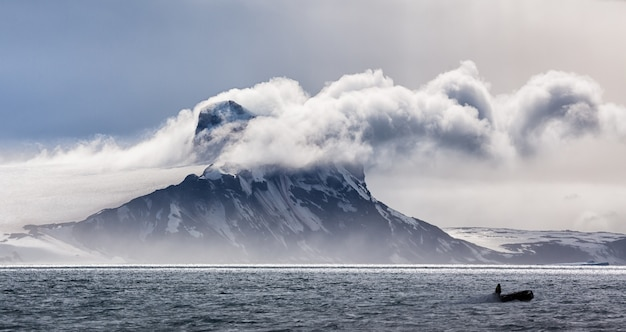 Panoramic view of an iceberg in clouds in antarctica