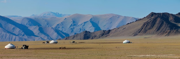 Panoramic view of mongolian nature with yurts and desert mountains