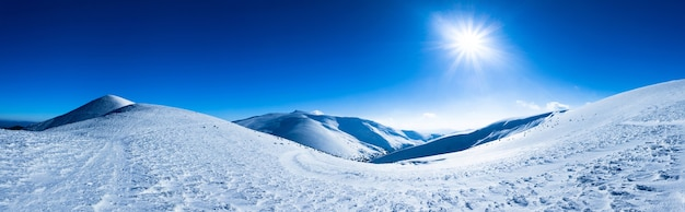 Panoramic view of mountains covered with snow on clear winter frosty day.