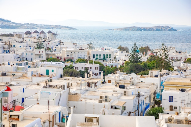 Panoramic view over mykonos town with white architecture and cruise liner in port, greece