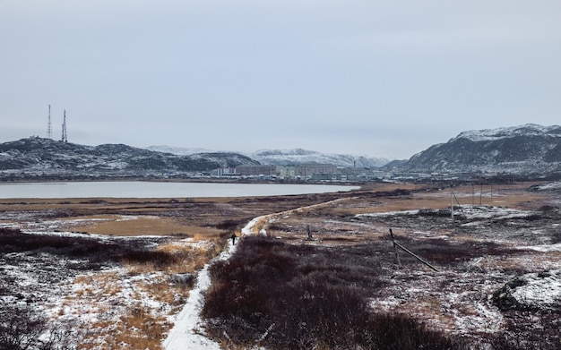 Panoramic view a narrow path that goes into the distance to the arctic village located between the polar hills