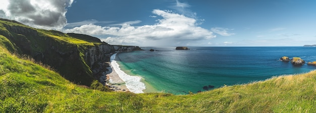Panoramic view of the northern ireland shoreline. cozy bay surrounded by the green grass covered irish land. overview of the white sand beach. the bright blue sky with the white clouds. wilderness.