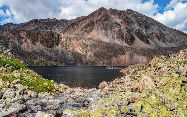 山々を背景に、手が届きにくい澄んだ山の湖を一望できます。高地の谷に湖がある大気の緑の風景。アルタイ山脈。