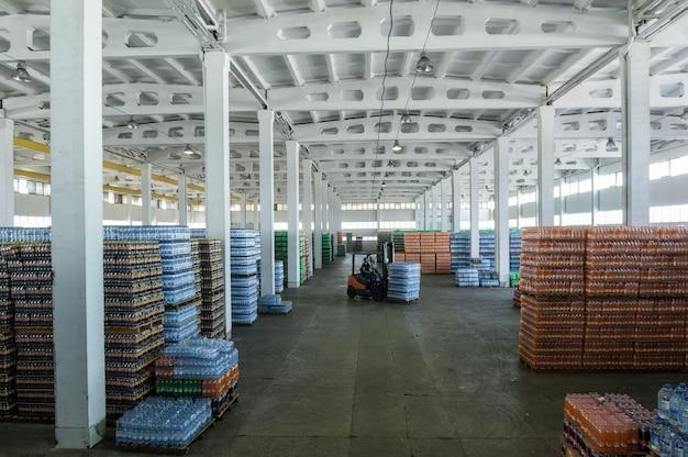 Панорамный вид на большой склад с напитками в пластиковых бутылках с загрузочными машинами