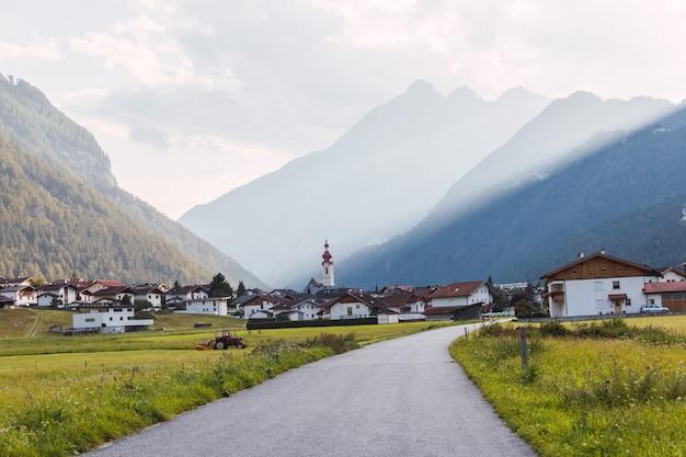 Панорамный вид на деревню в австрийских альпах с дороги с солнечными полосами, проходящей через горы