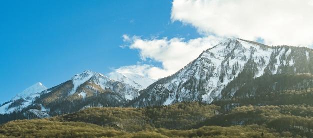 冬の日の青空にクラスナヤポリャナ村からアイブガ山の尾根のパノラマビュー。ソチ、ロシア