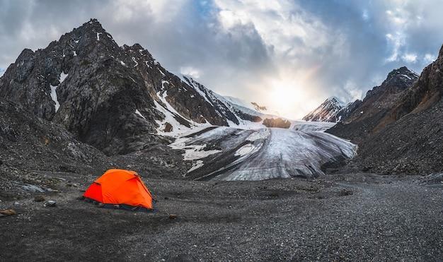 Панорамный вид оранжевого укрепленного шатра на фоне ледника на высокогорном плато. экстремальная ночевка в горах.