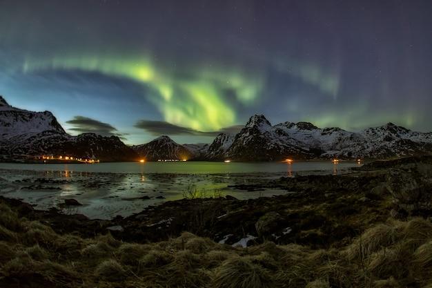 Панорамный вид на северное сияние над горами и озером