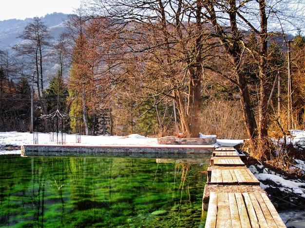 湖、木々、古い橋のある秋または冬の風景のパノラマビュー