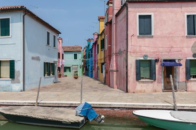 부라노(burano)에 있는 보트가 있는 밝은 색상의 집과 수로의 탁 트인 전망은 베네치아 석호(venetian lagoon)에 있는 섬입니다. 여름 화창한 날과 푸른 하늘