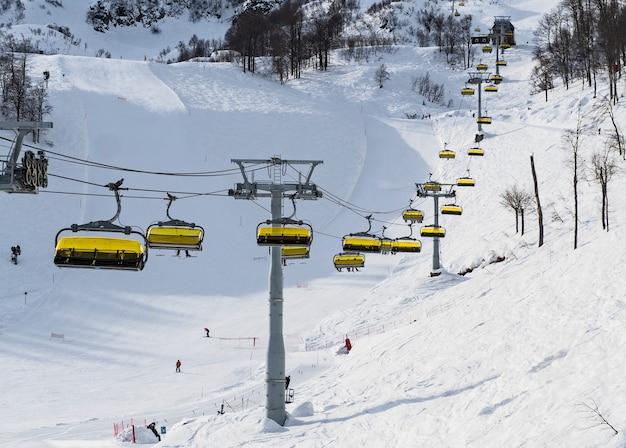 Панорамный вид кресельной канатной дороги на горнолыжных склонах и фоне гор на горнолыжном курорте роза хутор. сочи, россия