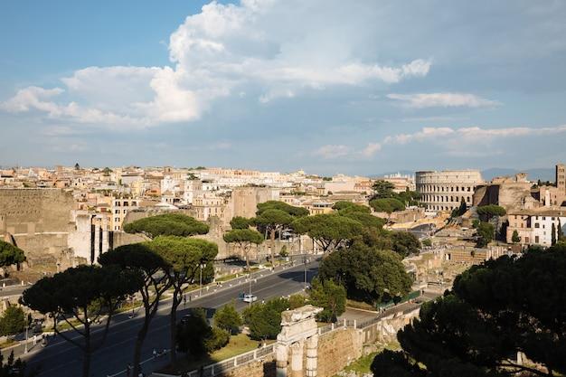 Панорамный вид на город рим с римским форумом и колизеем с памятника витторио эмануэле ii, также известного как витториано. летний солнечный день и драматическое голубое небо