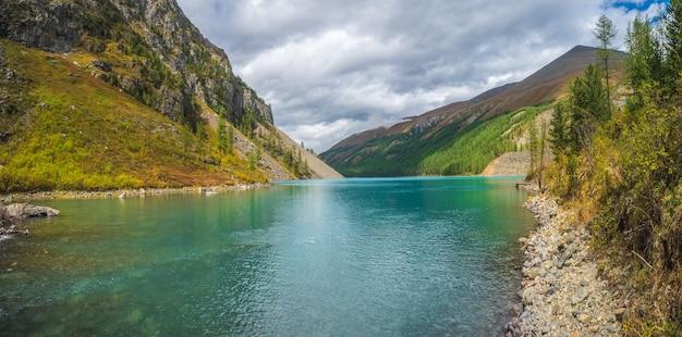 Панорамный вид на чистое горное озеро в лесу среди елей на солнце. яркие пейзажи с красивым бирюзовым озером на фоне заснеженных гор. нижнее озеро шавлин.