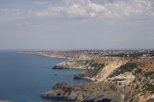 평화로운 푸른 바다로 작은 마을이있는 험준한 해안선의 전경. 흐린 여름 날에 바다 경치와 긴 험준한 해안. 자연, 해변, 휴가, 휴가 및 관광 목적지 개념