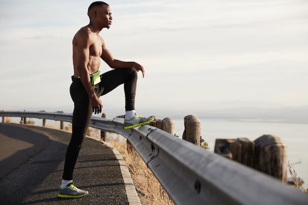 단호한 육체적 활동적인 청년의 전경은 고속도로에서 토플리스로 서 있고, 도로 표지판에 다리를 올리고, 아침에 운동을하고, 자연을 존경하고, 스포츠를 좋아하고, 피곤함을 느끼고, 에너지가 필요합니다.