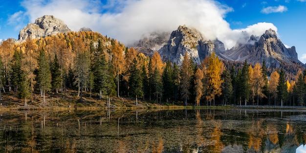 ドロミテ岩山とカラフルな木々の秋のアントルノ湖のパノラマビュー