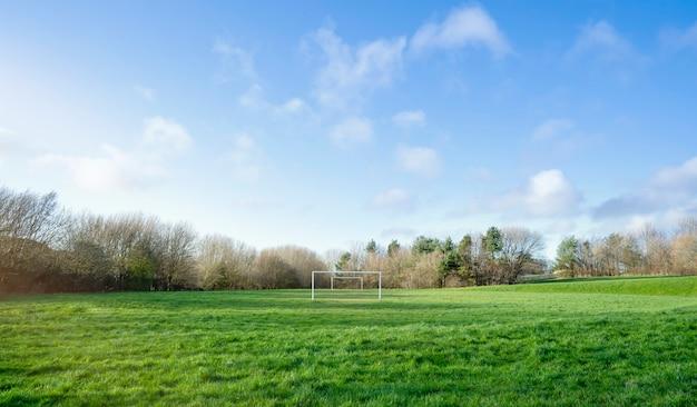 Панорамный взгляд футбольного поля в весне солнечного дня предыдущей, ландшафта футбольного поля в конце зимы. посты цели на зеленой траве с пасмурным и голубым небом.