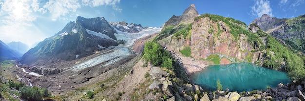 Панорамный вид на вершины ледников и озеро в горах кавказа