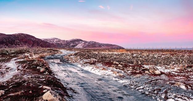 ツンドラを通る氷のように滑りやすい北極圏の道路のパノラマビュー。北の冬の道。マゼンタの極地の夕日。冬のテリベルカ。