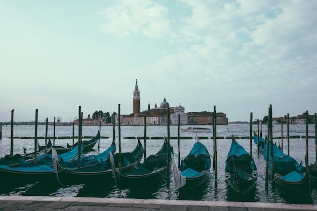 Панорамный вид на лагуна венета города венеции с гондолами и остров сан-джорджо маджоре вдалеке. пейзаж летнего утреннего дня и драматического голубого неба