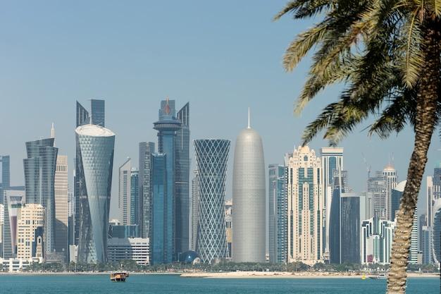 Панорамный вид современного горизонта дохи сквозь размытые пальмы. катар в солнечный день.