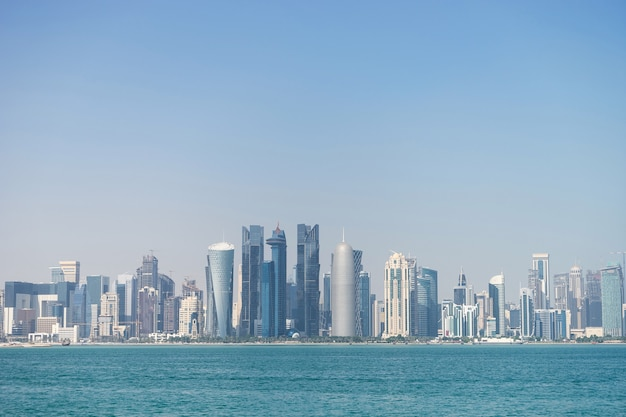 Панорамный вид на современный горизонт дохи через голубую воду.