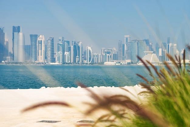 Панорамный вид на современный горизонт дохи с зеленой травой и пляжем на переднем плане. концепция здоровой окружающей среды.