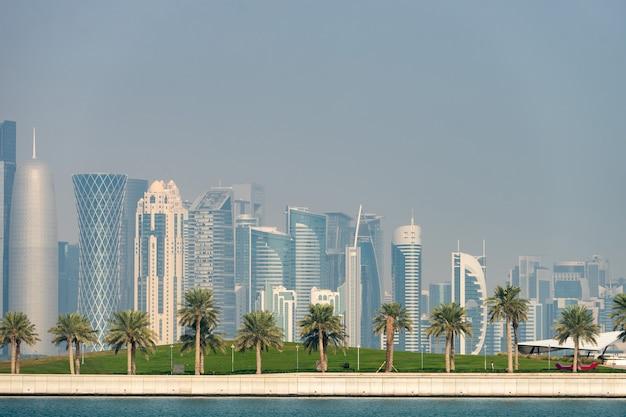 Панорамный вид на современный горизонт дохи с пальмами на переднем плане. концепция здоровой окружающей среды.