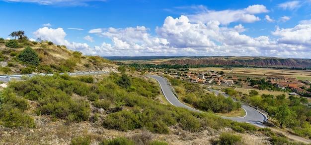 谷の背景に小さな町と山道のパノラマビュー。