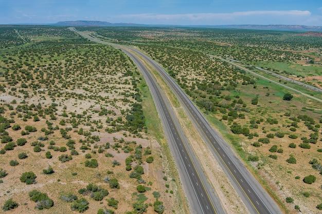 風光明媚な道路に捨てられた空のこの長い砂漠の高速道路上のニューメキシコのパノラマビュー