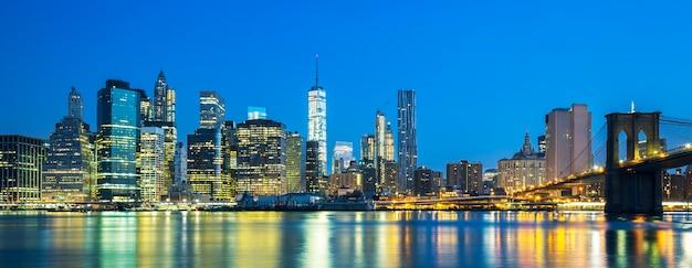 Панорамный вид на центр манхэттена нью-йорка в сумерках с небоскребами, освещенными над ист-ривер