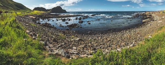 Панорамный вид на залив северной ирландии, потрясающий берег, окруженный валунами, покрытыми травой
