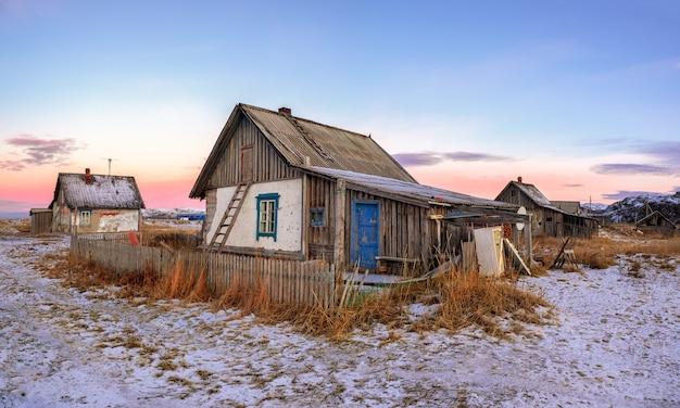 北極の空を背景にした古い家のパノラマビュー。テリベルカの古い本物の村。コラ半島。ロシア。