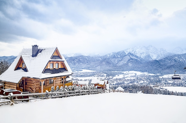 경치 좋은 겨울 원더 랜드 풍경 구름 언덕 꼭대기에 앉아있는 오래된 전통 농가의 전경