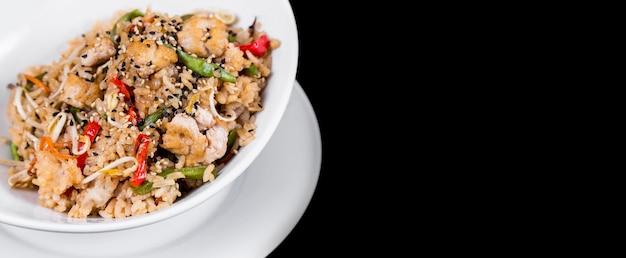 Панорамный вид восточного блюда из риса на черном фоне. международная кухня, восточные вкусы.