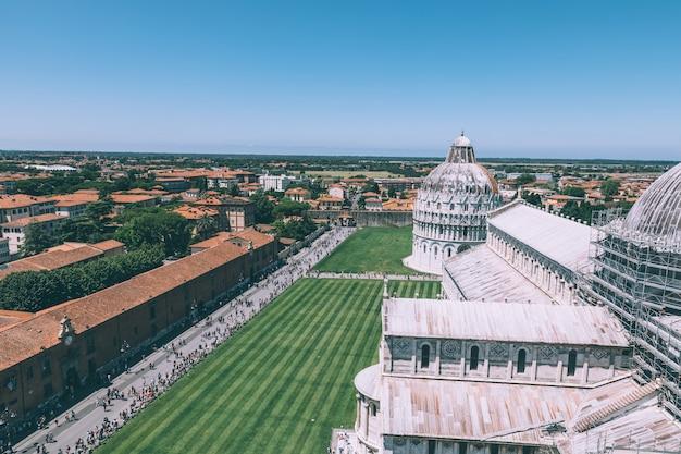 Панорамный вид на пьяцца дель мираколи с пизанским баптистерием святого иоанна и пизанский собор с пизанской башни. люди ходят и отдыхают на площади