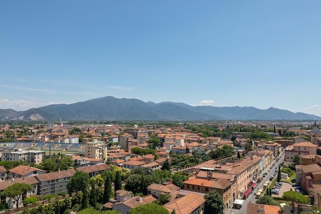 Панорамный вид на город пиза с историческими зданиями и далекими горами с пизанской башни. летний день и солнечное голубое небо