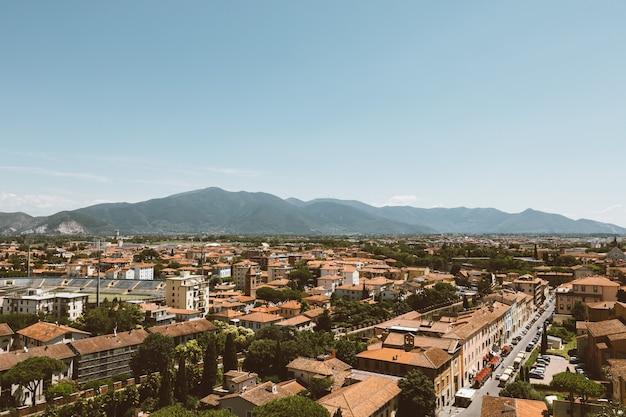유서 깊은 건물과 피사의 탑(tower of pisa)에서 멀리 떨어진 산이 있는 피사(pisa) 시의 탁 트인 전망. 여름날과 맑은 푸른 하늘