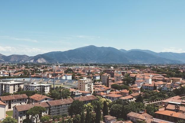 유서 깊은 건물과 피사의 탑에서 멀리 떨어진 산이 있는 피사 시의 탁 트인 전망. 여름날과 맑은 푸른 하늘