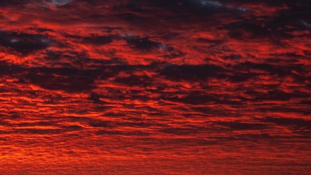 赤い夜の空のパノラマビュー。夕暮れ時のカラフルな曇り空。空のテクスチャ、抽象的な性質の背景