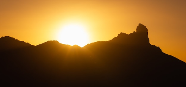 Панорамный вид на силуэт горы роке нубло на закате на канарских островах