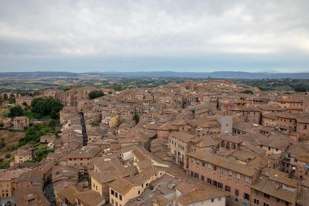 Панорамный вид на город сиена с историческими зданиями и далекими зелеными полями от torre del mangia - это башня в городе. летний солнечный день и драматическое голубое небо