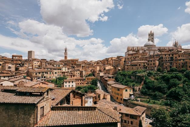 Панорамный вид на город сиена с историческими зданиями и далеким сиенским собором (duomo di siena). летний солнечный день и драматическое голубое небо